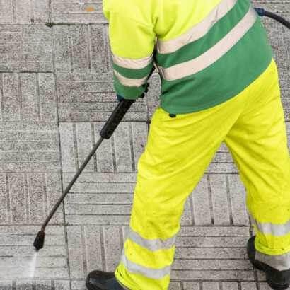 一個穿黃衣服的清潔工拿著高壓水槍清潔地板
