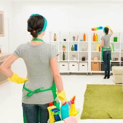 拿著清潔工具的女人看著另一個拿著毛撢的女人掃櫃子