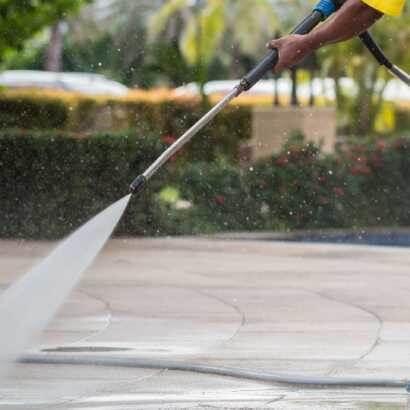 有隻手拿著高壓水柱沖洗地板