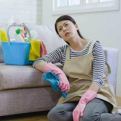 一個疲累的女人癱坐在放有清潔工具的沙發旁