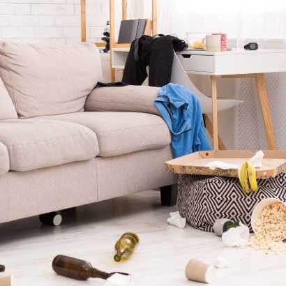 沙發旁有散亂一地的酒瓶爆米花垃圾等,以及亂放的衣服