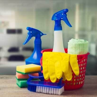 桌上放著一組菜瓜布、手套、刷子以及清潔劑的清潔用具
