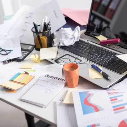 筆、紙類文件、杯子及垃圾散落在電腦辦公桌上