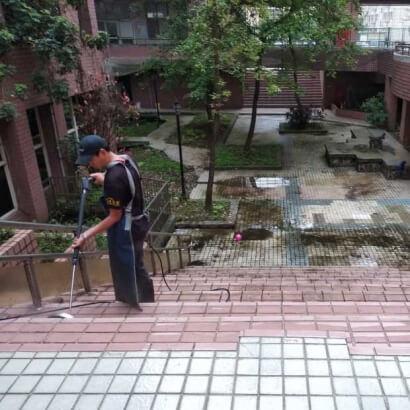 一個男人拿著高壓水柱沖洗校園樓梯